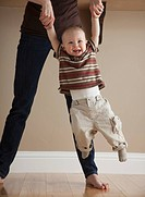 Mother swinging toddler