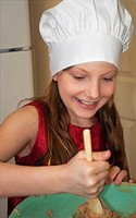 This cute 9 year old Caucasian girl is happy and smiling as she's stiring a batch of cookie dough with a wooden spoon in a green bowl She's wearing a ...