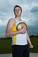 Male athlete posing with discus