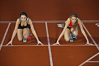 2 female athletes in starting blocks