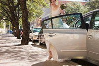 bride stepping out of car before wedding