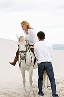 White horse, blond woman with teacher, beach, sea
