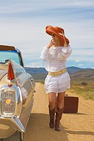 Lonely woman on desert road hitch hiking, classic convertible car stops