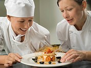 Two female chefs admiring a pudding