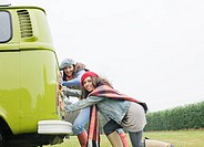 Women pushing camper van