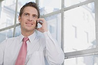 Germany, Munich, business man using mobile phone, smiling, portrait