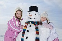 Germany, Bavaria, Munich, Two girls 4_5 8_9 standing next to snowman, smiling, portrait