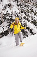 Young woman with snowboard and ski sticks