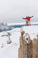 Italy, South Tyrol, Couple in winter clothes on mountain top, cheering
