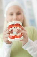 Germany, Bavaria, Landsberg, Girl 8_9 holding model of teeth