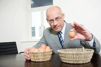 Germany, Munich, Businessman holding an egg, portrait