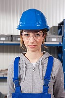 Germany, Neukirch, Young woman wearing hardhat and safety glasses, portrait