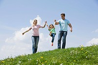 Germany, Bavaria, Munich, Parents with child 6_7 walking in meadow