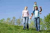 Germany, Bavaria, Munich, Family walking in meadow, father carrying daughter 6_7 on shoulders, portrait