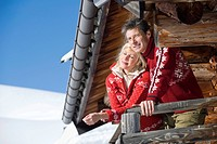 Italy, South Tyrol, Seiseralm, Couple standing on deck of log cabin