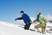 Italy, South Tyrol, Seiseralm, Senior couple walking in snow, side view, portrait