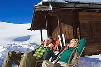 Italy, South Tyrol, Seiseralm, Couple resting in chairs by log cabin