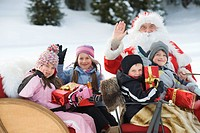 Italy, South Tyrol, Seiseralm, Santa Claus and children taking a sleigh ride