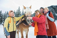 Italy, South Tyrol, Seiseralm, Family standing by horse, smiling, portrait