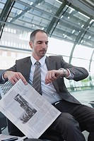 Germany, Leipzig, Businessman in Airport departure lounge, holding newspaper