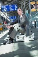 Germany, Leipzig_Halle, Airport, Businessman sitting on suitcase