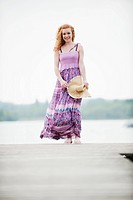 Germany, Bavaria, Ammersee, Young woman standing on jetty, holding hat, portrait