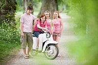 Germany, Bavaria, Four friends standing by moped, portrait