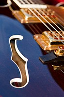 The violin hole and pickups/strings on an electric guitar Gretsch - detail