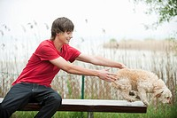 Germany, Bavaria, Ammersee, Young man and dog on bench, portrait