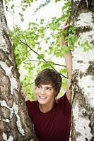 Germany, Bavaria, Young man leaning on tree, portrait