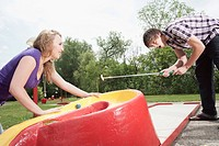 Germany, Bavaria, Ammersee, Young couple playing mini golf