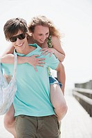 Germany, Bavaria, Ammersee, Young man giving young woman a piggy back on jetty, portrait