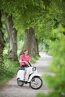 Germany, Bavaria, Young man on moped, smiling, portrait
