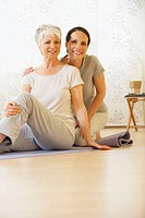 Two women sitting on gym mat, smiling, portrait