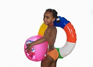 African girl 6_7 holding floating tire and beach ball, side view, portrait