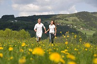 Austria, Young couple walking through meadow