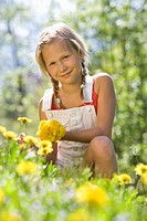 Austria, Salzkammergut, Girl 10_11 plucking flowers, portrait