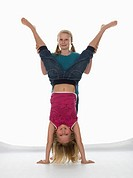 Two girls 10_11 one of them doing handstand, portrait