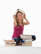 Portrait of a girl 10_11 with stacked books, one book on head