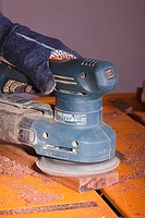 An orbital sander being used to finish a section of timber