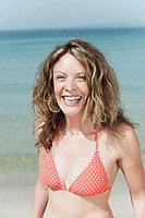 Spain, Mallorca, Woman on beach, laughing, portrait