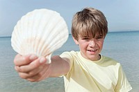 Spain, Mallorca, Boy 8_9 holding shell on beach, portrait