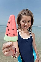 Spain, Mallorca, Girl 10_11 holding ice cream on beach, portrait