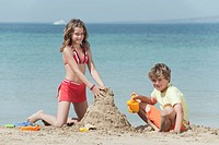 Spain, Mallorca, Children building sandcastle on beach