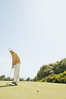 Spain, Mallorca, Senior man playing golf, side view