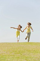 Spain, Mallorca, Mother and daughter 10-11 running in meadow (thumbnail)