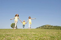 Spain, Mallorca, Mother and children 4-5, 10-11, walking across meadow (thumbnail)