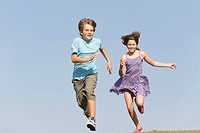 Boy 8_9 and girl 10_11 running toghether