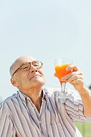 Spain, Mallorca, Senior man holding glass with orange juice, portrait