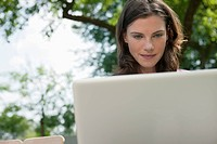 Germany, Hamburg, Woman using laptop in garden (thumbnail)